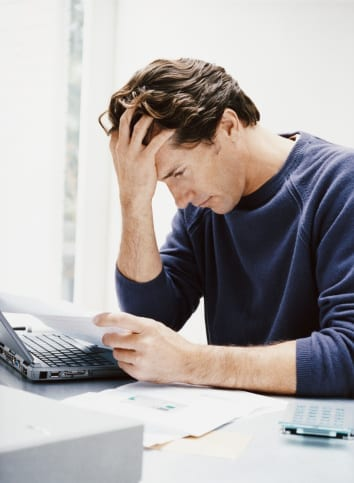 Man concentrating with his hand on his head