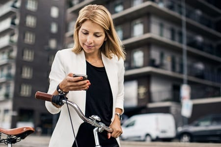 Businesswoman using smart phone in city